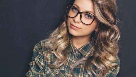 Young woman wearing glasses with dark background