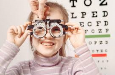Child holding eye exam equipment