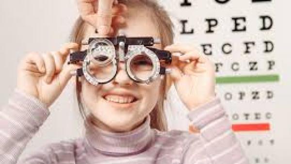 Child holding eye exam equipment