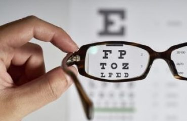 Eye exam chart shown through glasses lens